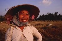 Vietnam, Outside Vinh Long, Mekong delta, Smiling rice farmer at rice harvest / threshing time. - Martin Westlake