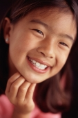 Young girl smiling with hand on chin - Mary Grace Long