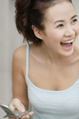 Young woman holding cellular phone, laughing - Erik Soh