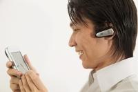 Man using PDA, smiling - Erik Soh