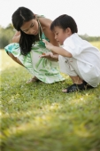 Mother and son crouching on lawn, looking at a seed. - Alex Microstock02