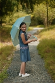 Young girl holding an umbrella, looking over shoulder - Alex Microstock02