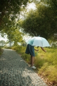 Young girl holding an umbrella, bending to look at something - Alex Microstock02