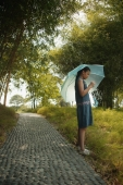 Young girl holding an umbrella, looking at something - Alex Microstock02