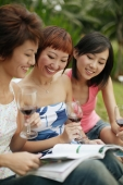 Young women browsing through magazine, wine glasses in hand - Alex Microstock02