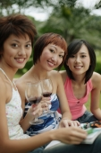 Young women sitting, looking at camera, wine glasses in hand - Alex Microstock02