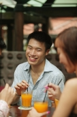 Young man sitting with friends, having a drink - Alex Microstock02