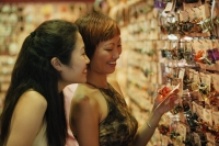 Two women in shop, looking at hair accessories - Alex Microstock02