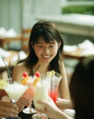 Young woman and friends toasting with drinks. - Alex Microstock02