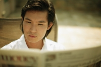 Young man reading newspaper - Alex Microstock02