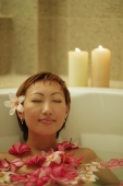Woman relaxing in tub, flowers floating around her - Alex Microstock02