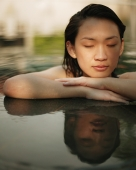 Young woman, at edge of swimming pool, eyes closed - Alex Microstock02