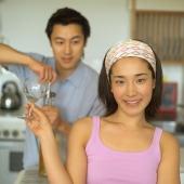 Couple in kitchen, man opening wine bottle, woman holding wine glass - Eckersley/Peacock