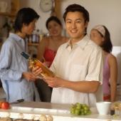 Friends in the kitchen, talking, man holding wine bottle - Eckersley/Peacock