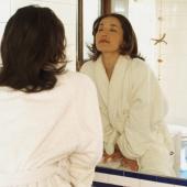 Young woman in bathrobe, looking at mirror - Eckersley/Peacock
