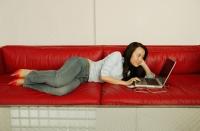 Woman on sofa, using laptop - Eckersley/Peacock