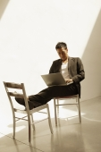 Man sitting down, using laptop - Eckersley/Peacock