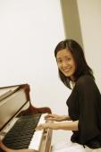 Woman at piano, looking at camera - Eckersley/Peacock