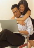 Man using laptop, woman hugging him - Eckersley/Peacock