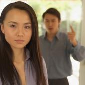 Woman looking at camera, man behind her gesturing - Eckersley/Peacock