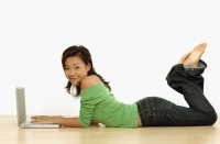 Young woman using laptop, lying on floor - Erik Soh