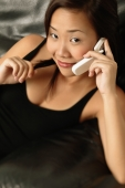 Young woman using a mobile phone, smiling - Erik Soh