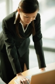 Young woman standing, using laptop - Alex Microstock02