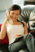 Young woman on sofa, holding phone and reading magazine - Alex Microstock02
