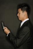 Young man using mobile phone, text messaging - Alex Microstock02
