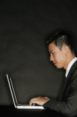 Young man using laptop, side view - Alex Microstock02