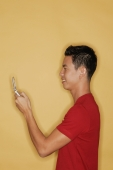 Young man holding mobile phone, profile - Alex Microstock02