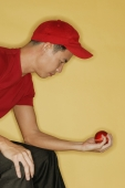 Young man sitting down and holding a ball in his hand - Alex Microstock02