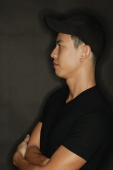 Young man with arms crossed, black background - Alex Microstock02