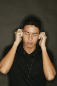 Young man using headphones, black background - Alex Microstock02