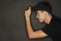 Young man touching cap, black background - Alex Microstock02