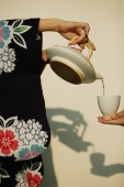 Young woman in kimono pouring tea for someone. - Alex Microstock02