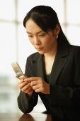 Young woman sitting at desk, using mobile phone - Alex Microstock02