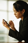 Young woman sitting at desk, using PDA - Alex Microstock02
