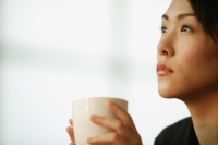 Young woman sitting at desk, holding mug - Alex Microstock02