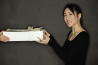 Young woman holding a gift, black background - Alex Microstock02