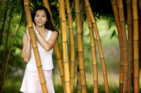 Young woman standing in a bamboo grove, smiling - Jack Hollingsworth
