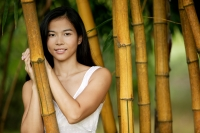 Young woman standing amongst bamboo canes, smiling - Jack Hollingsworth