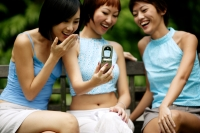 Three young women sitting side by side, using camera phone - Jack Hollingsworth