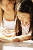 Mother and daughter, side by side, looking at magazine - Alex Microstock02