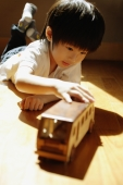 Young boy playing with toy bus, lying on front - Alex Microstock02