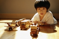 Young boy looking at camera, toys in a row in front of him - Alex Microstock02
