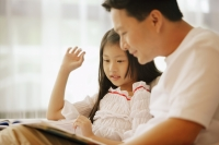 Father and daughter, sitting side by side, looking at book - Alex Microstock02