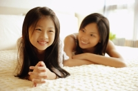 Mother and daughter lying on bed, smiling - Alex Microstock02
