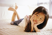 Young girl with hands on chin, lying on bed, looking away - Alex Microstock02