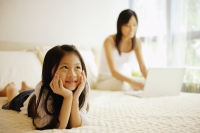 Mother and daughter in bedroom, mother using laptop - Alex Microstock02